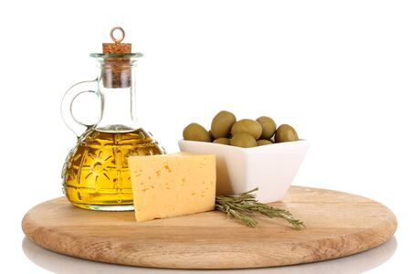 Green olives in white bowl with rosemary,olive oil and cheese on board isolated on white photo