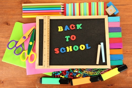 Small chalkboard with school supplies on wooden background. Back to School Stock Photo - 15410449