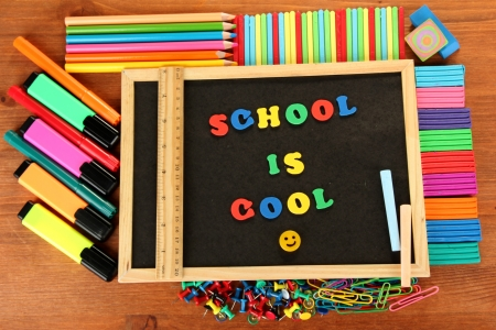 Small chalkboard with school supplies on wooden background. Back to School Stock Photo - 15397913