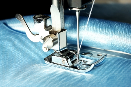 Sewing machine with blue cloth closeup photo