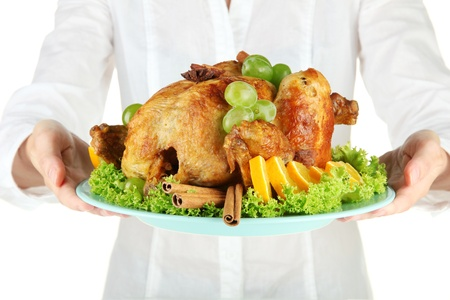 Chef holding a plate of baked chicken with fruit and spices close-up photo