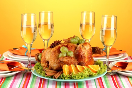 banquet table with roast chicken on orange background close-up. Thanksgiving Day photo