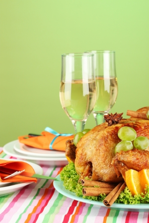 banquet table with roast chicken on green background close-up. Thanksgiving Day photo