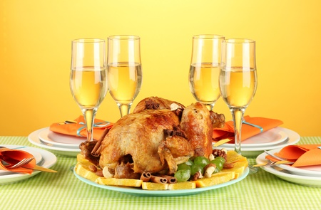 banquet table with roasted chicken on orange background close-up. Thanksgiving Day photo