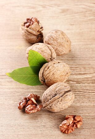 walnuts with green leaves, on wooden background Stock Photo - 15408946