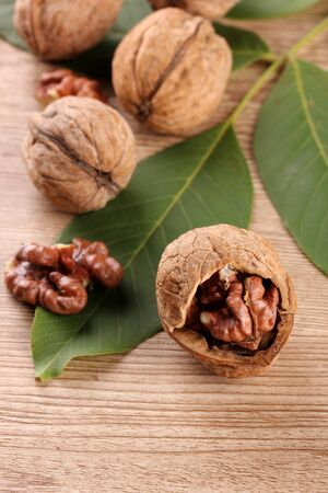 walnuts with green leaves, on wooden background Stock Photo - 15409307