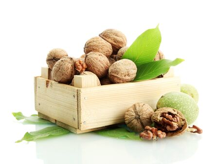 walnuts with green leaves in woooden crate, isolated on white Stock Photo - 15388962