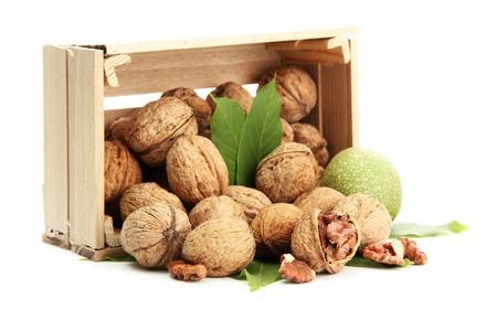 walnoten met groene bladeren in woooden krat, geïsoleerd op wit