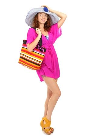 Een glimlachende mooi meisje met strand hoed en strand tas op wit wordt geïsoleerd Stockfoto