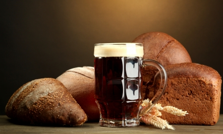 tankard of kvass and rye breads with ears, on wooden table on brown background Stock Photo - 15390990