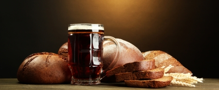 tankard of kvass and rye breads with ears, on wooden table on brown background Stock Photo - 15389929