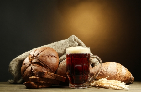 tankard of kvass and rye breads with ears, on wooden table on brown background photo