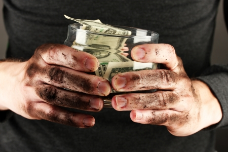 waster: homeless holds bank with money, close-up