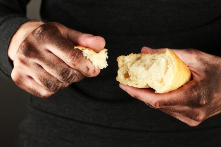 waster: homeless man holding a white bread, close-up