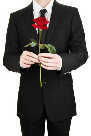 gift behind back: man holding rose close-up