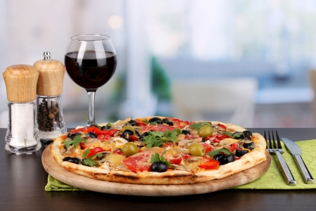 Delicious pizza with glass of red wine and spices on wooden table on room background