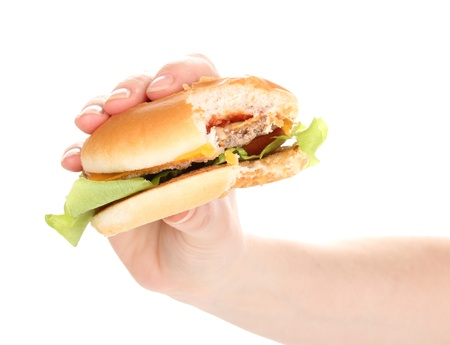 Bitten cheeseburger in hand isolated on white photo