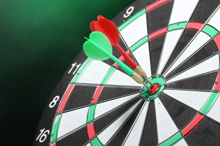 dart board with darts on green background photo