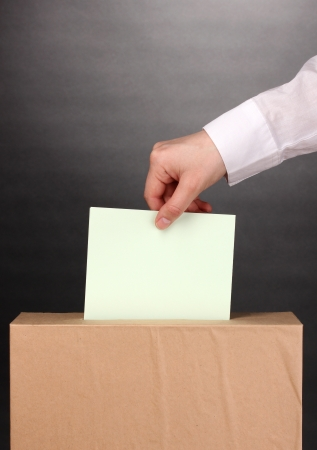 Hand with voting ballot and box on grey background Stock Photo - 15524046