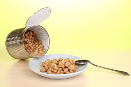Open tin can and plate with bean and spoon on wooden table on green background Stock Photo - 15396060