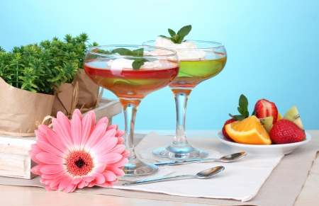 fruit jelly in glasses and fruits on table on blue background photo