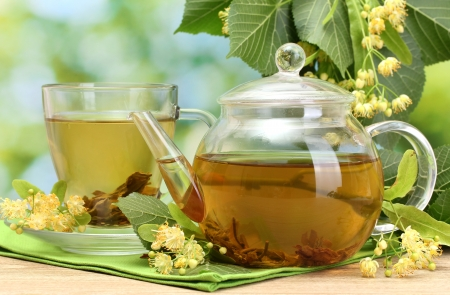teapot and cup with linden tea and flowers on wooden table in garden Stock Photo - 15420211