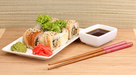 Tasty rolls served on white plate with chopsticks on wooden table on light background Stock Photo - 15529593
