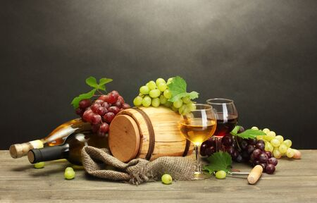 barrel, bottles and glasses of wine and ripe grapes on wooden table on grey background Stock Photo - 15420228