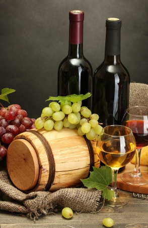 barrel, bottles and glasses of wine, cheese and ripe grapes on wooden table on grey background Stock Photo - 15423296