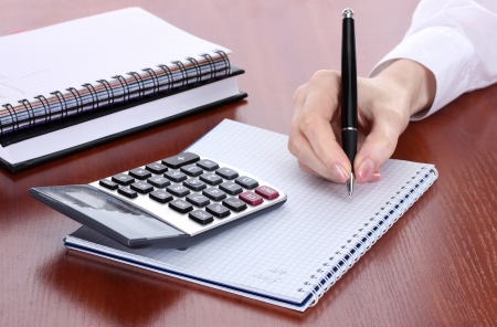 close up woman: women hands with pencil, notebooks and Calculator on wooden table Stock Photo