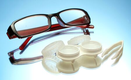 glasses, contact lenses in containers and tweezers on blue background photo