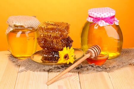 Jars of honey and honeycomb on wooden table on orange background photo