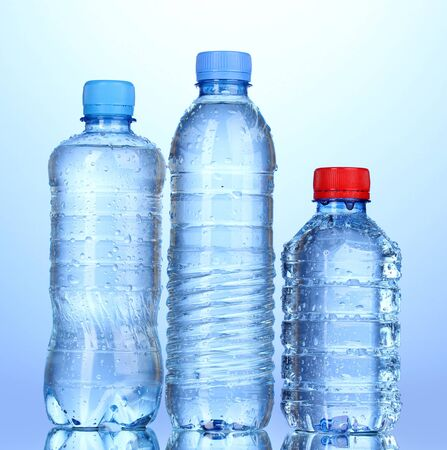 plastic bottles of water on blue background Stock Photo - 15416898