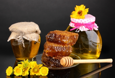 Jars of honey and honeycomb on black background