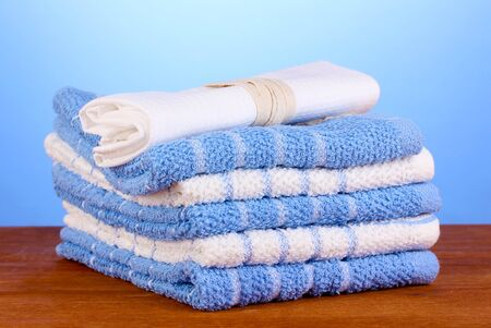 dishtowel: kitchen towels on wooden table on blue background close-up Stock Photo