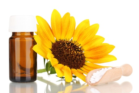 medicine bottle with tablets and flower isolated on white photo