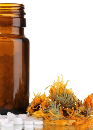 bottle with pills and herbs on white background. concept of homeopathy photo