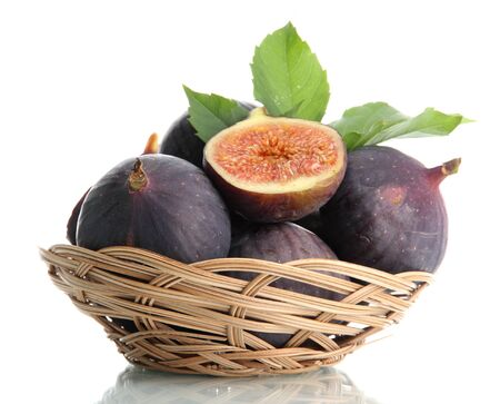 Ripe sweet figs with leaves in basket isolated on white photo