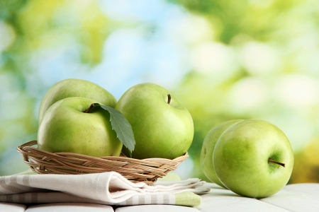Ripe green apples with leaves in basket, on wooden table, on green background Stock Photo - 15420268