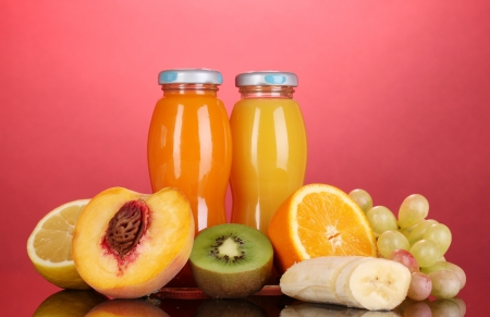 Delicious multifruit juice in a bottle and fruit next to it on pink background photo