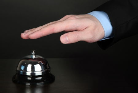 Hand ringing in service bell on wooden table on black background Stock Photo - 15420856