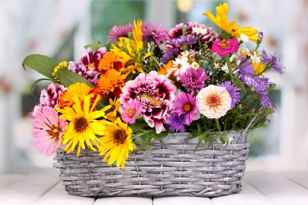 arrangement: beautiful bouquet of bright flowers in basket on wooden table Stock Photo