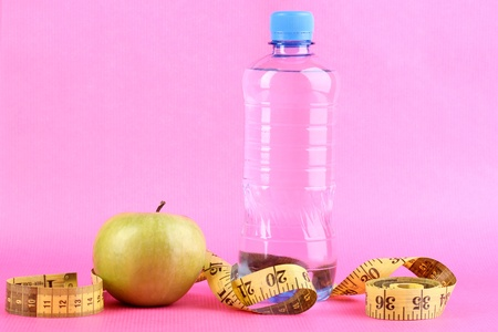 microelements: Bottle of water, apple and measuring tape on pink background Stock Photo