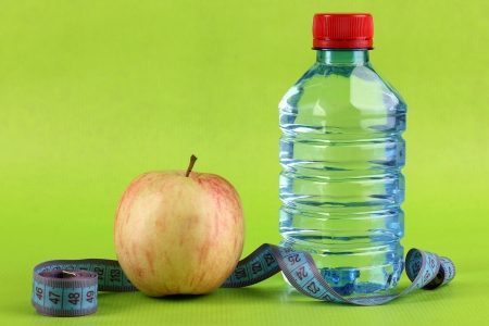 microelements: Bottle of water, apple and measuring tape on green background Stock Photo