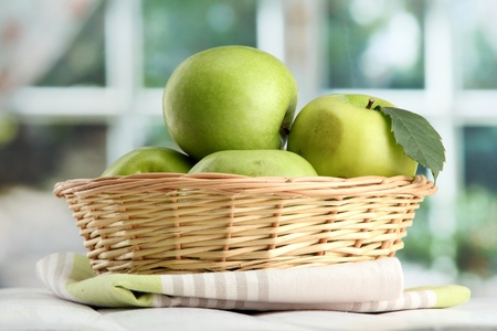 Ripe green apples with leaves in basket, on wooden table, on window background Stock Photo - 15425251