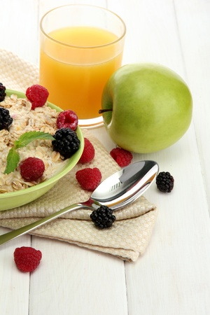 tasty oatmeal with berries and glass of juice, on white wooden table Stock Photo - 15425317