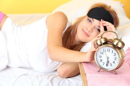 young beautiful woman lying on bed with eye mask and  alarm clock, on yellow background photo