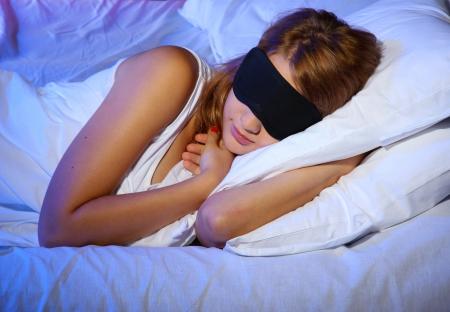 blonde yeux bleus: belle jeune femme avec masque de sommeil oeil sur lit dans la chambre