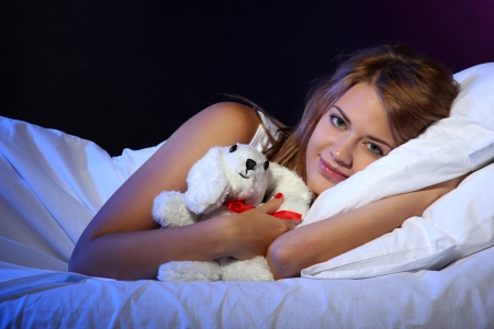 young beautiful woman with toy rabbit lying on bed in bedroom photo