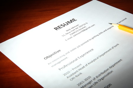 job recruitment: Closeup of resume with pencil on wooden table